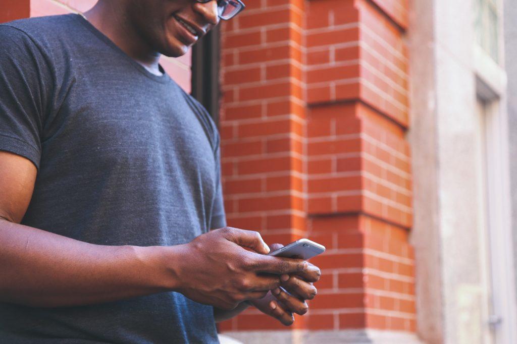 Homem em pé usando o melhor celular de até 1.000 reais