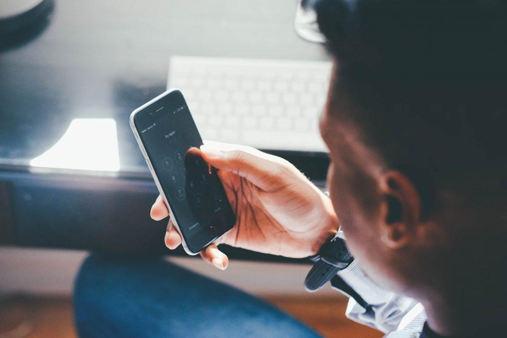 Homem sentado usando o melhor celular de até 1.000 reais