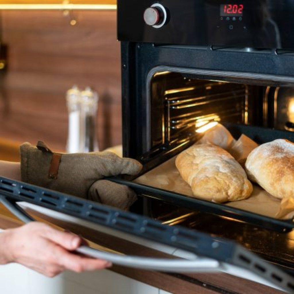 Pessoa retirando pães do melhor forno elétrico