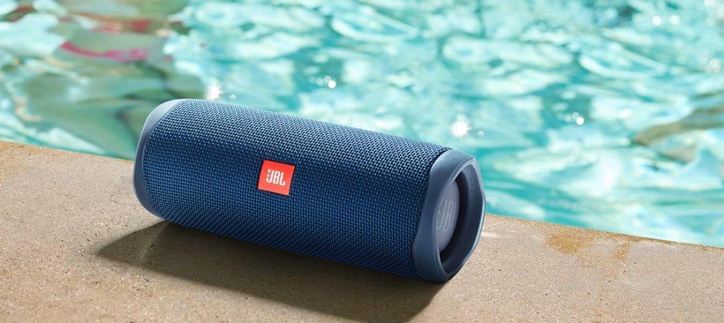 A melhor caixa de som JBL sendo usada na beira da piscina.