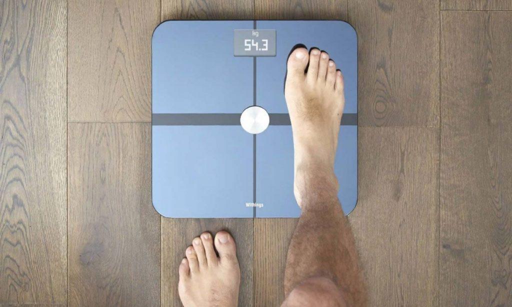 Homem se pesando na melhor balança de bioimpedância
