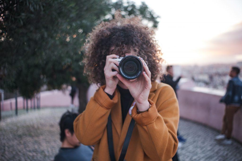 Jovem capturando um momento com uma câmera fotográfica profissional