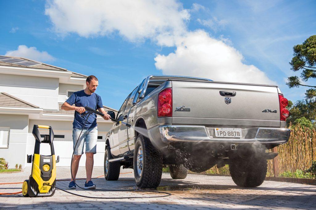 Homem usando a melhor lavadora de alta pressão na limpeza do carro.
