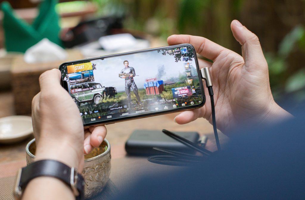 Mãos de homem segurando o melhor celular para jogos